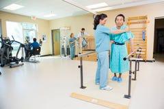 Thérapeutes aidant des patients dans le gymnase d'hôpital photo stock