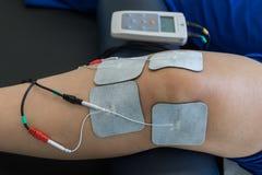 Thérapie électronique sur le genou employé pour traiter la douleur photographie stock libre de droits