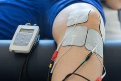 Thérapie électronique sur le genou employé pour traiter la douleur images stock