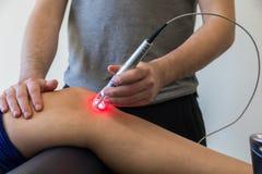 Thérapie de laser sur un genou employé pour traiter la douleur images stock