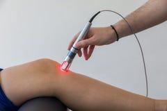 Thérapie de laser sur un genou employé pour traiter la douleur photo libre de droits