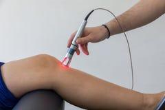 Thérapie de laser sur un genou employé pour traiter la douleur images libres de droits