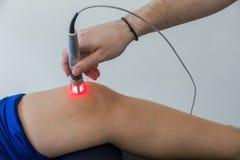 Thérapie de laser sur un genou employé pour traiter la douleur photos libres de droits