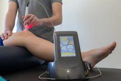 Thérapie de laser sur un genou employé pour traiter la douleur photographie stock libre de droits