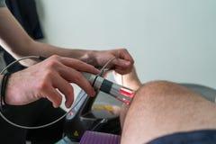 Thérapie de laser sur un genou employé pour traiter la douleur photo stock