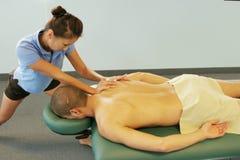 Thérapie de massage - thérapeute donnant le massage arrière image stock