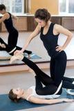 Thérapie de pratique femelle de yoga de deux yogis dans la classe Photo libre de droits