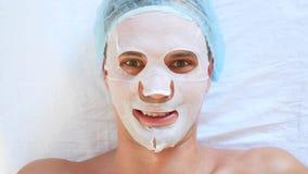 Thérapie de station thermale pour les hommes beaux recevant le masque facial 4K Mouvement lent Réception d'un cosmetologist clips vidéos