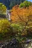 19th århundradekyrka av antagandet, floden och höstträdet i stad av Shiroka Laka, Bulgarien Fotografering för Bildbyråer