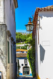 11th århundradelampa Obidos Portugal för smal vit gata Arkivbild