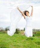 年轻愉快的妇女跳和拿着一块白色布在Th的 免版税库存图片
