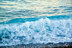 天蓝色的海波浪 与白色泡沫的清楚的大海 在Th的小卵石 库存图片