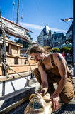 36th Annual Victoria Classic Boat Festival. A young man is polishing the bronze figurehead of his sailboat which is docked in front of the Empress Hotel. The Stock Photos