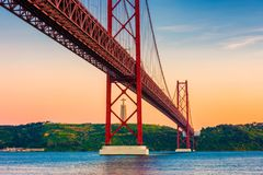 25th of April Bridge Lisbon Portugal at Sunset. 25th of April Bridge, Tagus River and Christ the King statue in Lisbon Portugal around sunset royalty free stock photography
