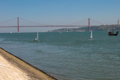 25th April Bridge in Lisbon and Sailing Boats, Portugal. 25th April Bridge in Lisbon over the Tagus River and Sailing Boats, Portugal Stock Image