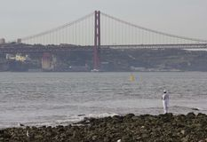 25th of April bridge seen from the stone beach Stock Photo