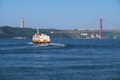 25th of April Bridge suspension bridge over river Tejo with ferr. Y and Jesus Christ the King Statue on background in Lisbon, Portugal Royalty Free Stock Images