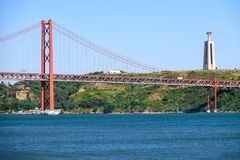 25th of April Bridge suspension bridge over river Tejo with Jesu. S Christ the King Statue on background in Lisbon, Portugal Royalty Free Stock Images