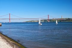 25th of April Bridge suspension bridge over river Tejo with Jesu. S Christ the King Statue on background in Lisbon, Portugal Royalty Free Stock Photos