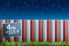 4th av det Juli kritatecknet på planka på gräset Royaltyfri Bild