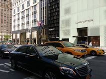 5th Avenue, New York City, NYC, NY, USA. Cars drive southbound, between 57th and 58th Streets, down one of New York City`s most famous, most expensive, and most Royalty Free Stock Images