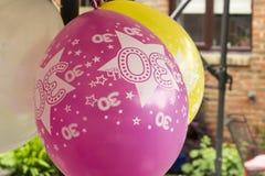 30th birthday balloons. Pink and yellow 30th birthday balloons Stock Photo