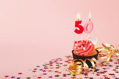 50th birthday cupcake with candle and sprinkles. 50th birthday cupcake with candles, sprinkles and ribbon on pink background. Card mockup, copy space. Birthday Stock Image