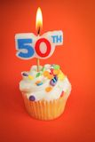 50th birthday. Delicious cupcake with 50th candle on top on orange background Stock Photo