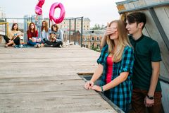 Birthday surprise rooftop party friends. 20th birthday surprise. Boy covering girl`s eyes. Rooftop party with friends Stock Photo