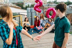 Birthday surprise rooftop party friends invite. 20th birthday surprise. Friends waiting for a girl with balloons. Celebration, congratulation Royalty Free Stock Photography