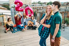 Birthday surprise rooftop party friends support. 20th birthday surprise. Girl is happy and smiling. Friends sit on a rooftop with balloons. Celebration Royalty Free Stock Photo
