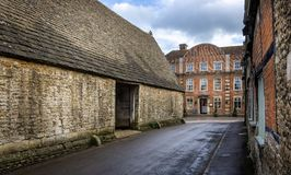14th Centruy Tithe Barn and The Red Lion Inn in Lacock, Wiltshire, UK. On 10 March 2019 royalty free stock images