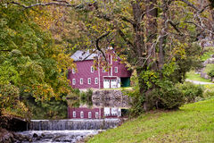 19th Century Barn In the Fall with Ond and waterfalls with rteflection in the pond of the barn NJ Royalty Free Stock Photos