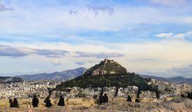 19th century Chapel of St. George on Mount Lycabettus viewed over the rooftops of Athens from the Acropolis with silhouettes o stock images