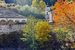 19th century Church of the Assumption, river and Autumn tree in town of Shiroka Laka, Bulgaria Royalty Free Stock Images