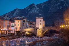 13th century historic toll bridge in Sospel, France. 13th century historic toll bridge over Bevera river at dusk in Sospel, Alpes-Maritimes, France stock photography