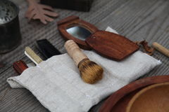 18th century male grooming kit. Shaving kit and personal items used in the 18th century. Tooth brush, shaving brush, mirror, in cloth holder.  Still life Royalty Free Stock Photos