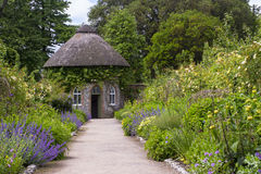 The 19th Century thatched round house surrounded by beautiful flower beds and gravel paths in the walled garden at West Dean garde Stock Image