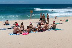 Young people celebrating Christmas eve on Bronte beach with Santa hats in Sydney NSW Australia royalty free stock image