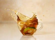 thé en verre d'éclaboussure de cuvette Boisson chaude de citron Images stock
