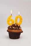 60th födelsedagmuffinkaka med stearinljus Arkivfoto