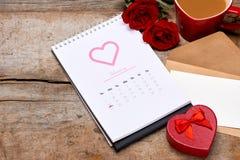 14th Februari på kalenderdatum Röd ros, hjärtor och gåva bo Arkivbild