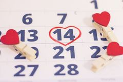 14th february on calendar. 14th February marked with a heart on calendar and wooden pins with red hearts. Close up. St.Valentine`s concept Stock Photo