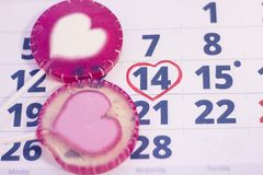 14th february on calendar. 14th February marked with a heart on calendar and pink lilopops with hearts. Close up. St.Valentine's concept Stock Photo