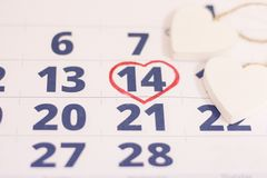 14th february on calendar. 14th February marked with a heart on calendar and wooden hearts. Close up. St.Valentine`s concept Stock Photography