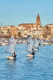 30th International Vila de Palamós Optimist Trophy, 14th Nations Cup. Sailboats sailing to the harbor small town Palamos in royalty free stock photo
