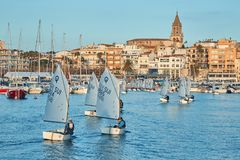 30th International Vila de Palamós Optimist Trophy, 14th Nations Cup. Sailboats sailing to the harbor small town Palamos in royalty free stock image