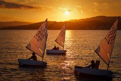 30th International Vila de Palamós Optimist Trophy, 14th Nations Cup. Sailboats sailing to the harbor small town Palamos in royalty free stock photography