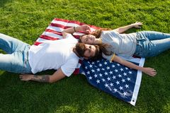 4th of July. American tradition. History of America. American patriotic people. American couple relaxing on USA flag royalty free stock photo