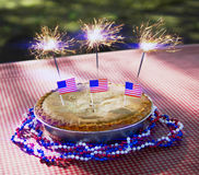 4th of July Apple Pie with Sparklers on a Table Royalty Free Stock Images